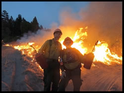 Jim Wills and Rick O'Rourke in firefighter dress and gear holding drip torches with flames from a prescribed burn blazing in the background.