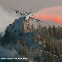 A National Guard aircraft making a slurry drop on a forest fire.