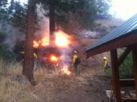Firefighters burning fuels near a structure.