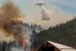 Aircraft making a retardent drop on an active wildfire.